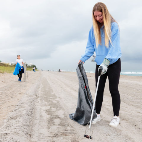 A student cleans up trash on the beach.
