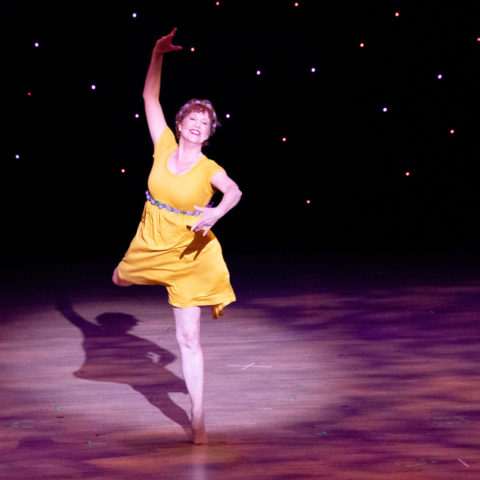 Becky Timms dances onstage in a yellow dress during Celebrati上 of the Arts 2019.